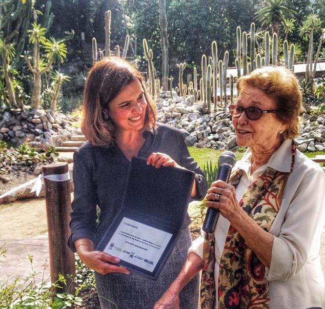 Adriana Pinto, presidente do Instituto Masan, entrega placa em homenagem à Cecilia.